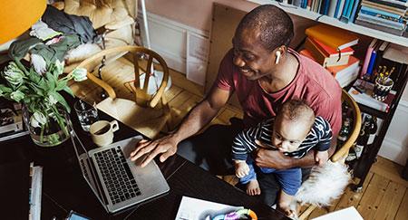 Lächelnder Geschäftsmann mit Laptop und Kleinkind im Home-Office
