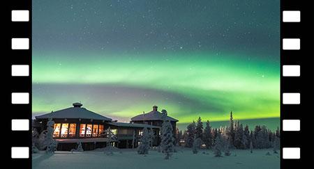 Zeitraffer der grünen Nordlichter am klaren Nachthimmel über einem alten, mit Schnee bedeckten Holzhaus in der verschneiten Landschaft in Yllas, Lappland (Finnland)