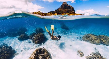 Une femme plongeant sous l'eau avec des palmes jaunes dans l'océan tropical de l'île Maurice.