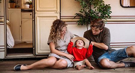 Parents assis avec leur jeune fils devant leur mobile-home en vacances.